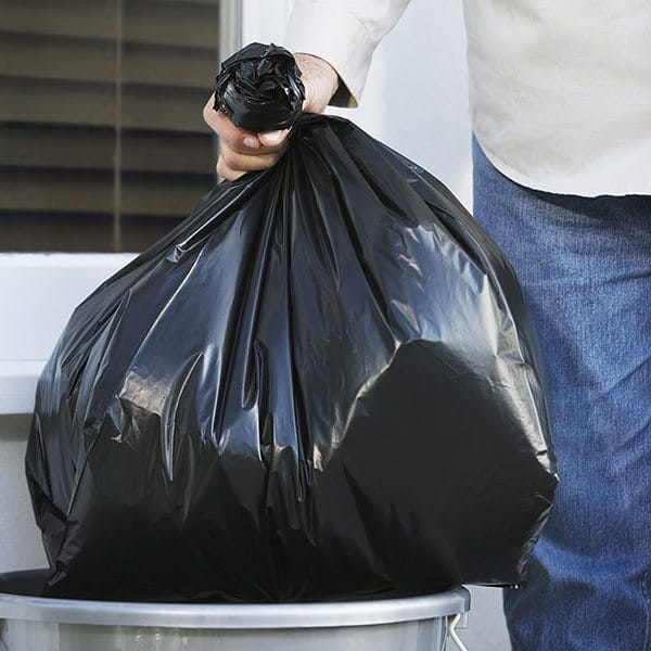 Hand Putting Garbage Bag Into Trash Can